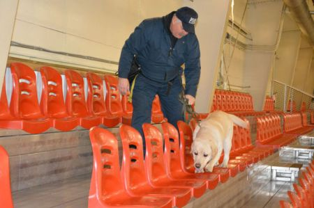 Gord Mellor of Devon's Rae-Tech Fire Investigations Ltd. coaches Sam the labrador to detect ignitable liquids during a training session at Devon's Dale Fisher Arena on Monday, Feb. 3.