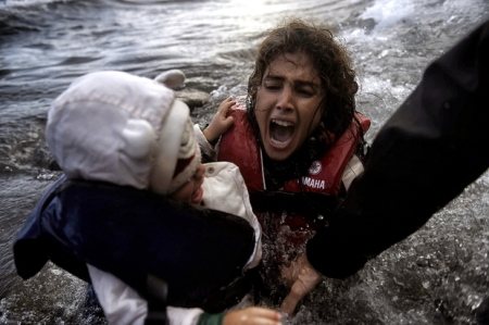 Photo: A woman falls into the water with her child as they disembark off a dinghi as refugees and migrants arrive at the Greek island of Lesbos after crossing the Aegean sea from Turkey, on October 2, 2015.Greece's prime minister told the United Nations on October 1, that Athens was doing all it could to help the refugee and migrant crisis, and criticized the building of walls to keep them out. Around 330,000 people, most of them Syrians, Iraqis and Afghans fleeing war, have arrived on Greek shores so far this year, with another 3,000 still arriving every day, UN figures show. AFP PHOTO / ARIS MESSINIS