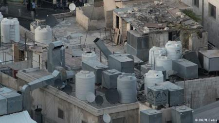 Water tanks crowd the rooftops of buildings in Jordan's water-parched capital of Amman
